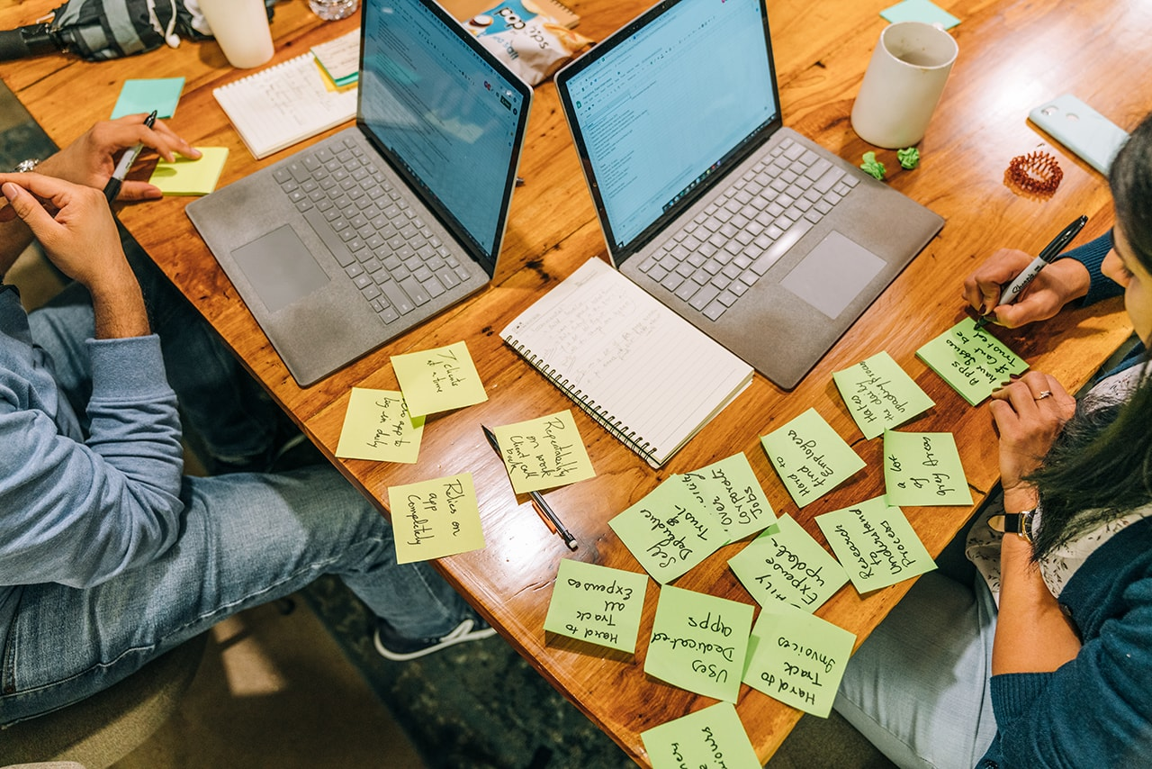 An overhead image of a conference room table filled with laptops, notebooks and sticky notes.