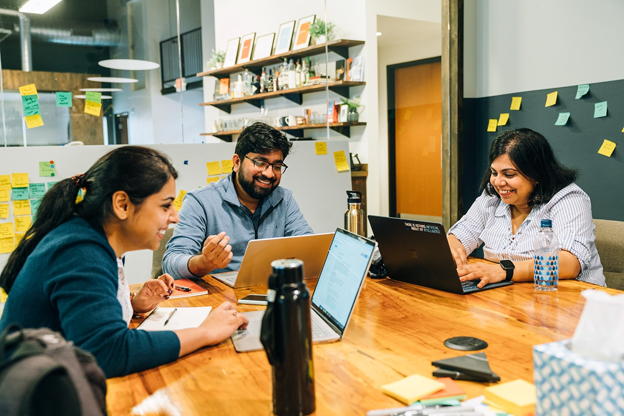 Three Broad MBA students work on laptops and collaborate in a bright, open conference room at Handsome agency.