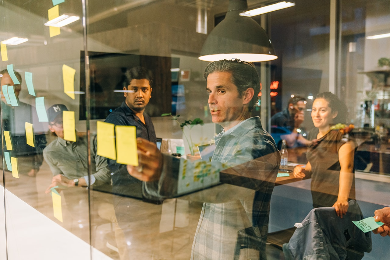 MBA students participate in design workshops and gain hands-on learning experiences using sticky notes in an exercise with Handsome's associate creative director of experience design and strategy Travis Rimel.