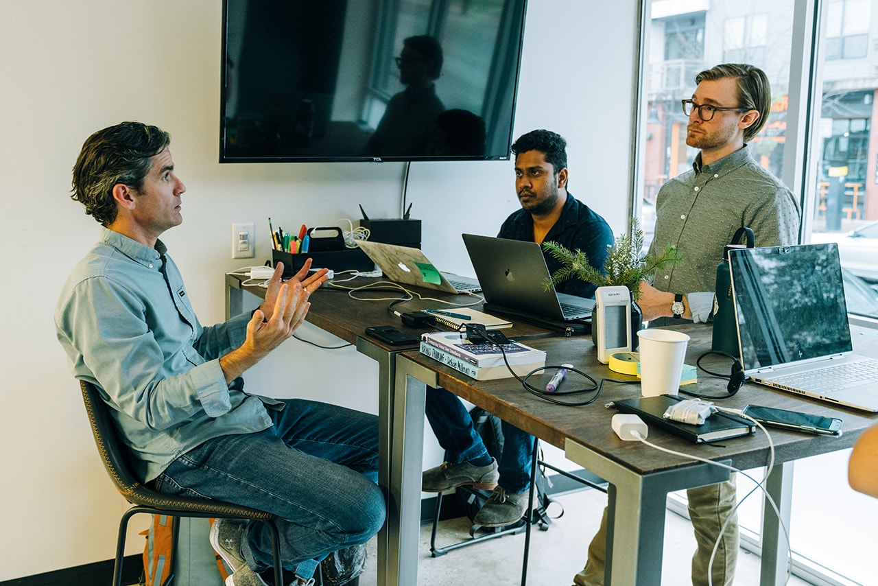 Broad MBA students talk with Handsome's associate creative director of experience design and strategy Travis Rimel in a small, open collaborative space.