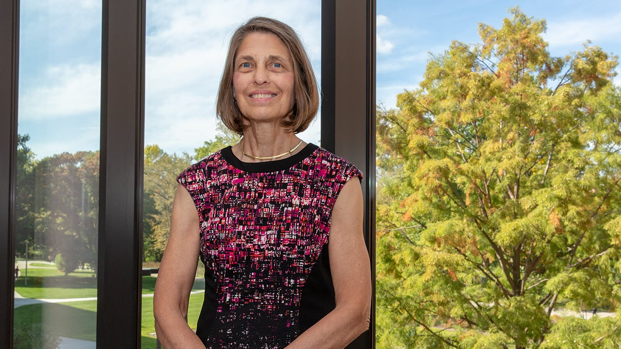 Professional image of Helen Dashney, fixed-term faculty in finance, in front of glass windows on a bright, sunny day.