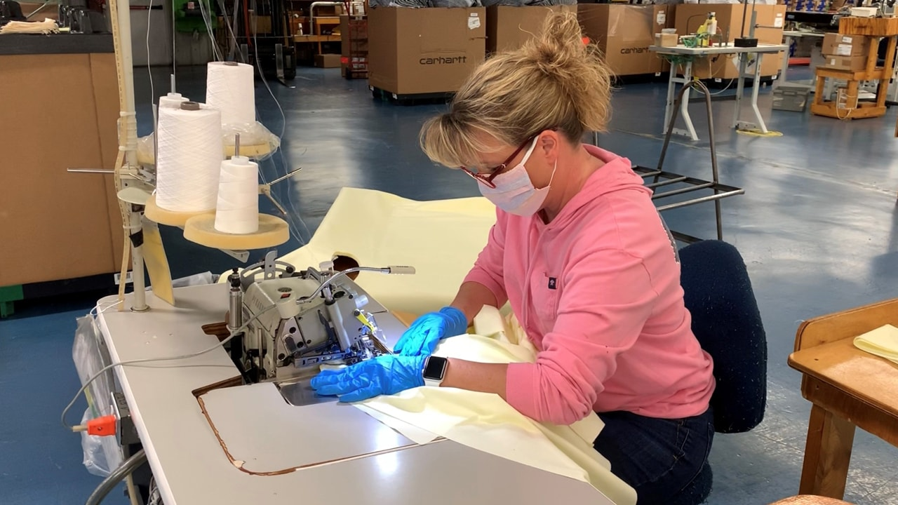 A female Carhartt employee seen at a work station sewing together a medical gown, wearing gloves and a face mask.