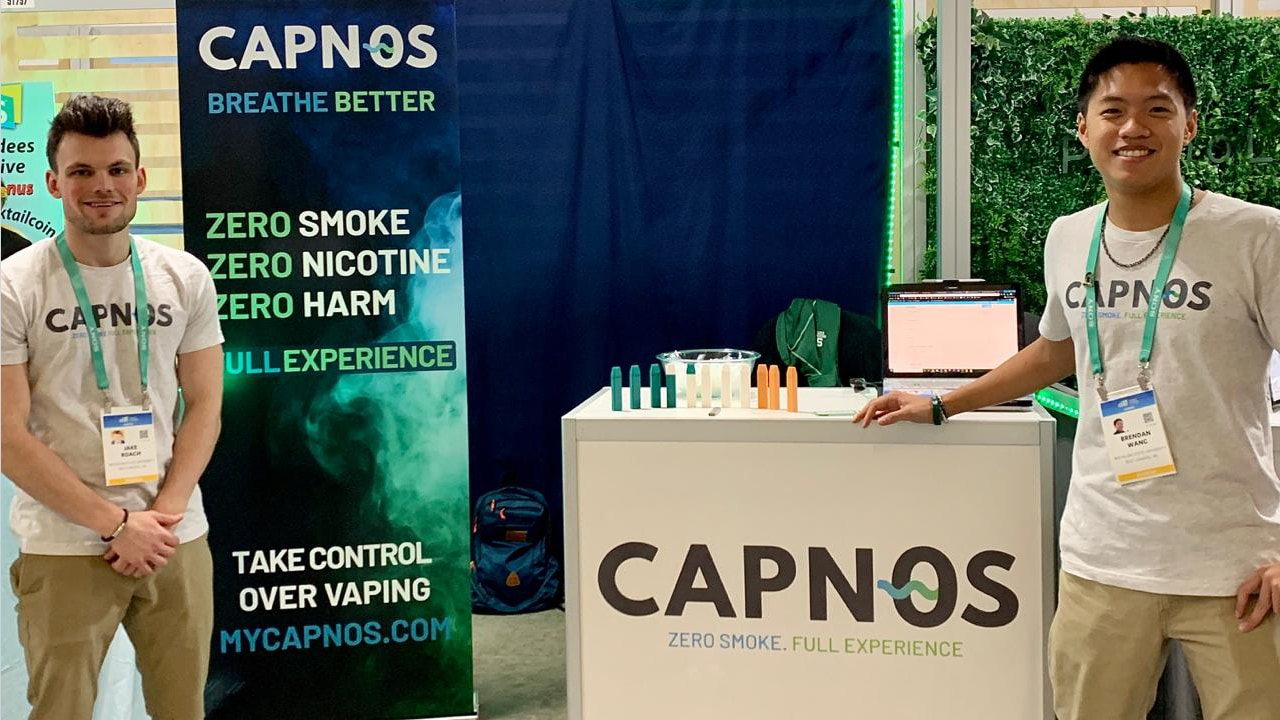 Jake Roach, marketing junior, and Brendan Wang, supply chain sophomore, stand at the CAPNOS corporate career both showcasing their safe alternative to vaping product at CES 2020.