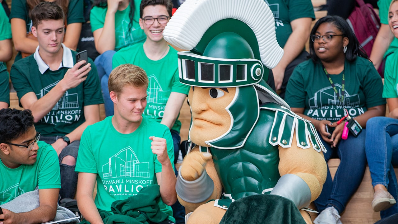 MSU's mascot, Sparty, fist bumps a student at the Ribbon-Cutting Ceremony.