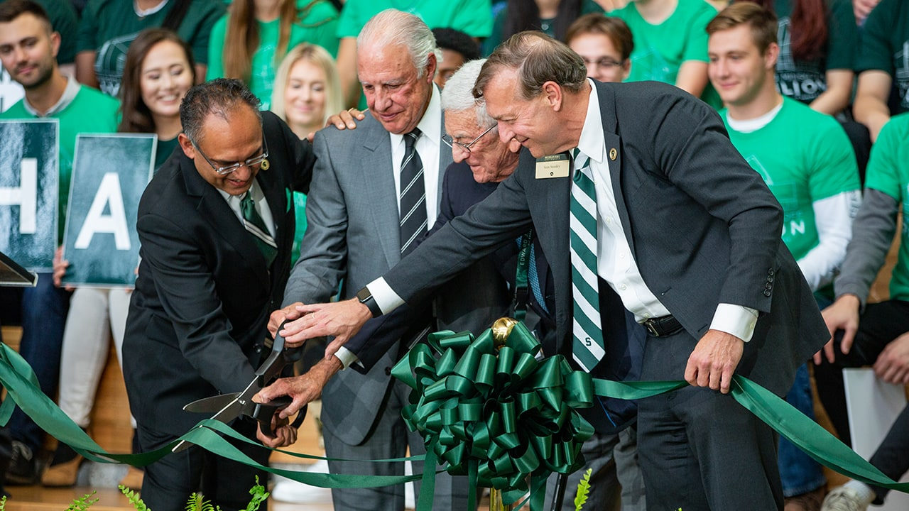 Broad College and MSU leaders alongside prominent alumni and donors, cutting a green ribbon with oversized scissors to mark the opening of the Minskoff Pavilion.