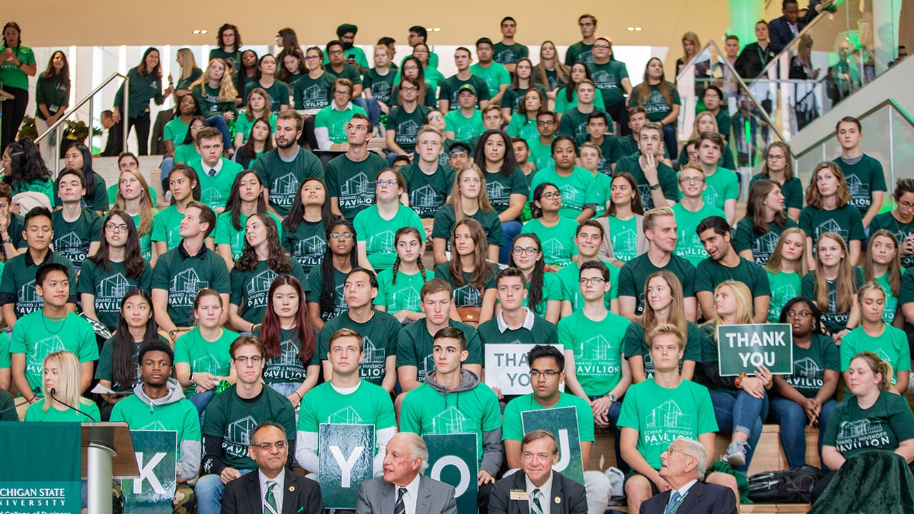 A view of the Grand Staircase in the Minskoff Pavilion filled with students wearing green t-shirts and holding signs for the celebration.