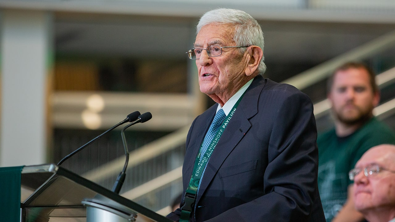 Eli Broad speaking at the podium at the Ribbon-Cutting Ceremony.