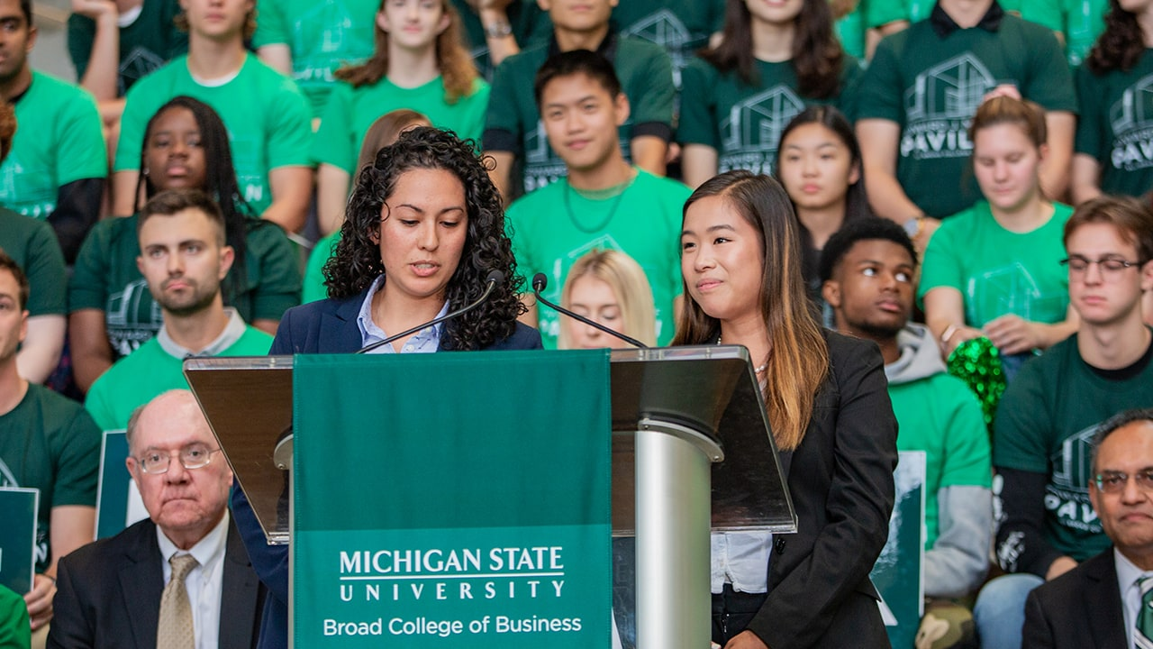 Two female students speak at the podium at the Ribbon-Cutting Ceremony.