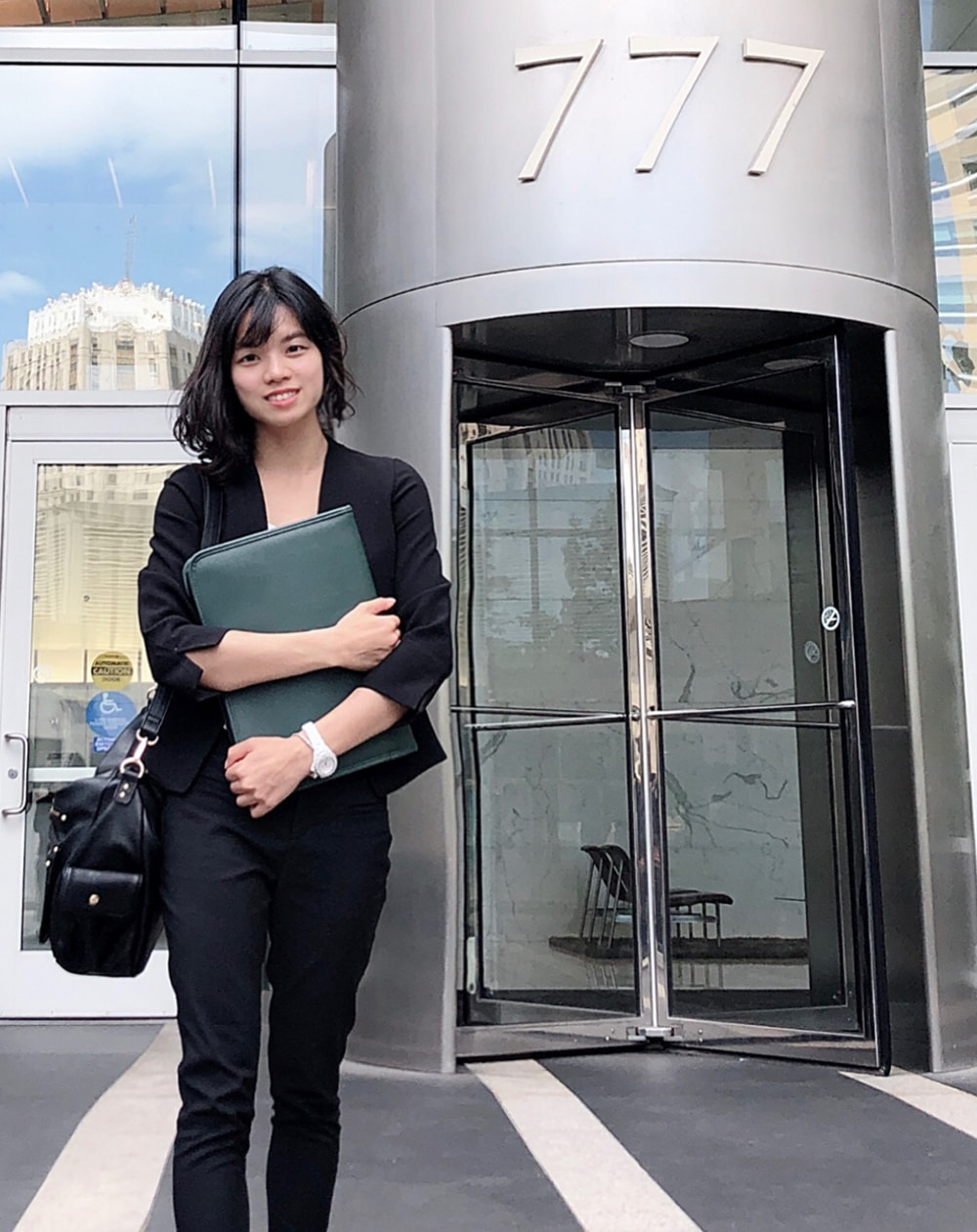 M.S. in Accounting student Daisy Wu pictured in professional attire outside of an office building.