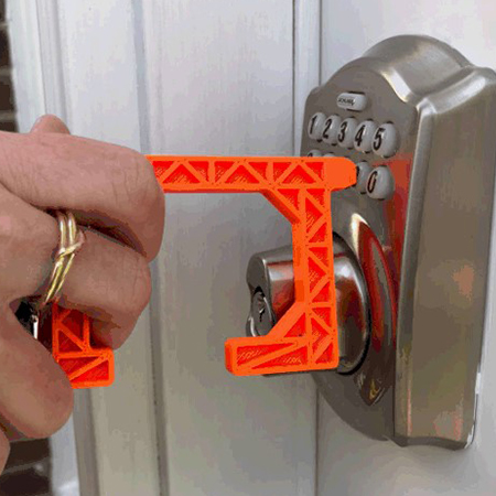 An orange version of the Spartan-designed No-Touch Tool being used to press a door-locking keypad.